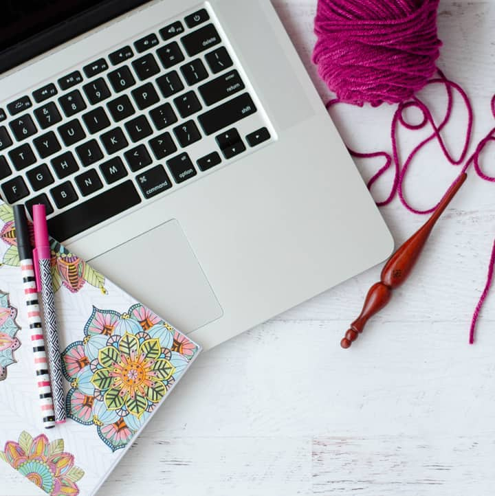 Should I Start a Blog? Laptop, floral notebook and pens, pink yarn and crochet hook