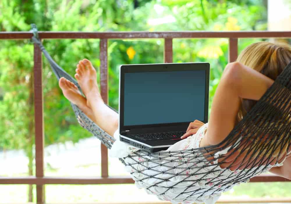 woman sitting in a hammock in a garden with laptop