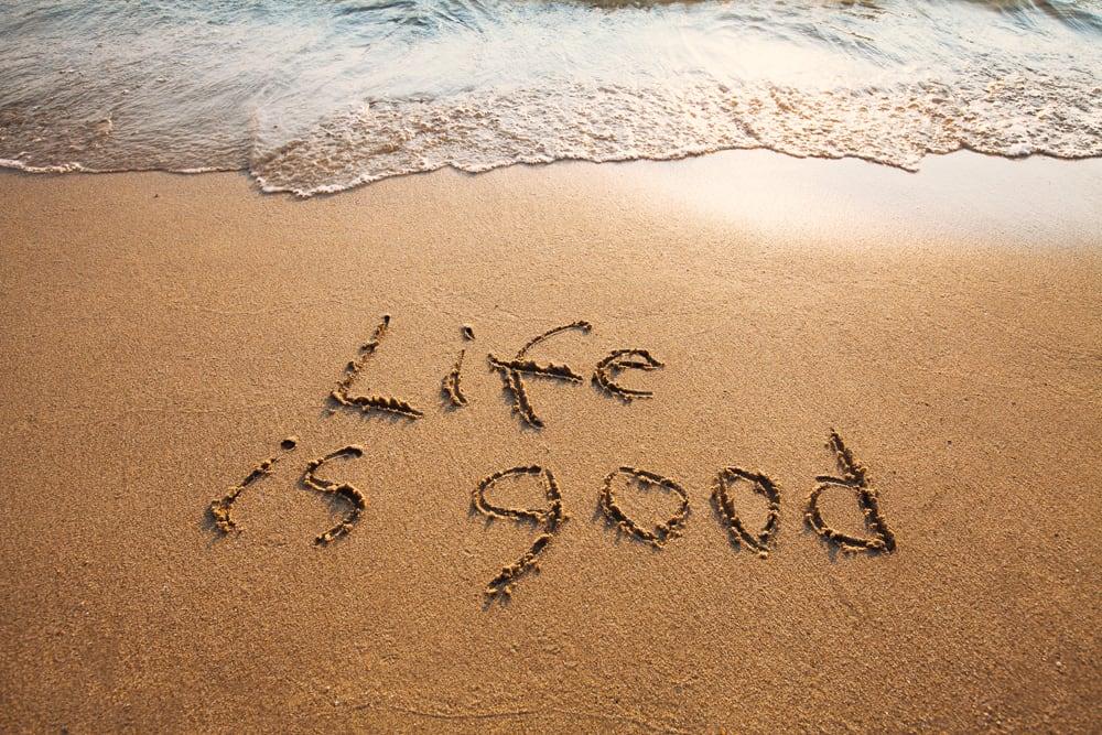 Life is good written in sand near water