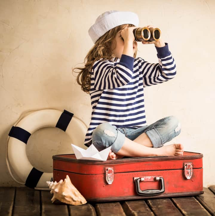 girl on suitcase with binoculars