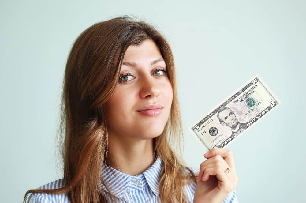 woman with a $5 bill