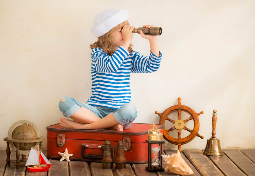 Girl on suitcase with nautical toys