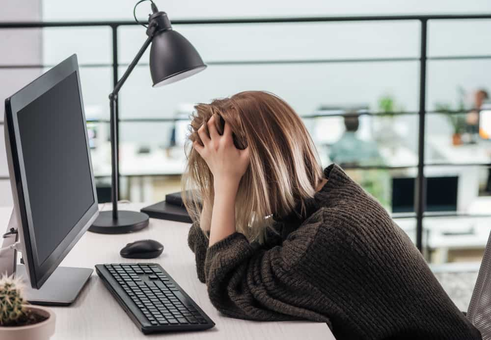 woman with head in hands leaned over computer